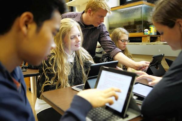 In this file photo, teacher Wes Molyneaux, center, helps students work through a lesson on their iPads in Anatomy & Physiology class in April of 2012 at New Trier High School in Winnetka.