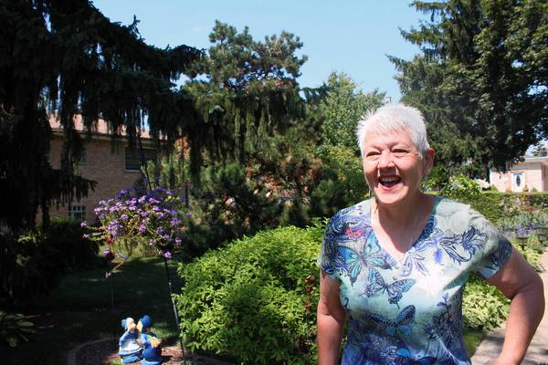 Carol Kala, president of the First Czechoslovak Garden Club of America, tends to a garden that includes flowers and trees planted by her grandfather in the 1930s.