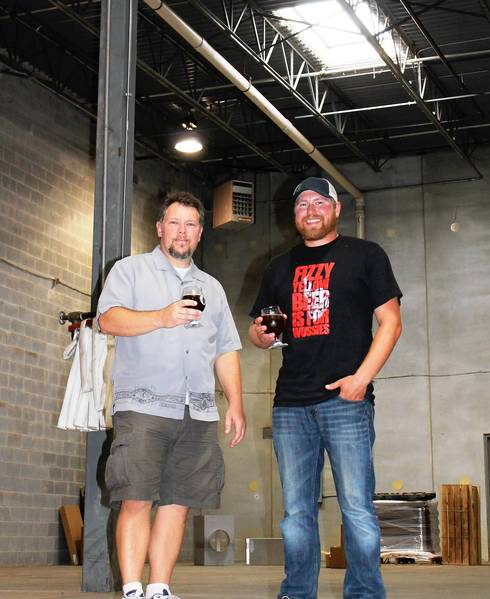 Chris Schiller, left, and Brandon Banbury toast the area that will be home to their Hailstorm Brewery in December with glasses of a home-brewed beverage. Retail sales will be limited to a tasting room.