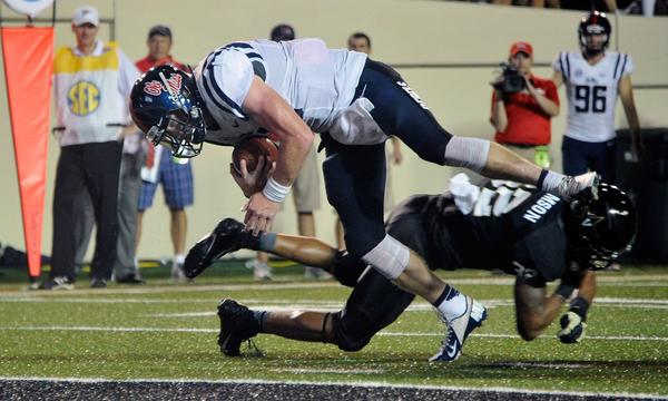Mississippi quarterback Bo Wallace dives over Vanderbilt's Andrew Williamson to score during the Rebels' victory Thursday night. It wasn't the only exciting game to kickoff the college football season.