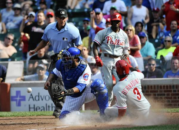 Aug 30, 2013; Chicago, IL, USA; Philadelphia Phillies center fielder Roger Bernadina (3) scores the winning run as Chicago Cubs catcher Dioner Navarro (30) tries to make a tag during the ninth inning at Wrigley Field.