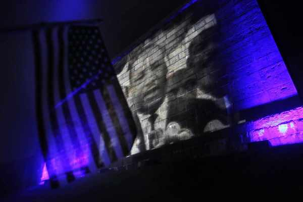 "A woman holds a U.S. flag as a video of Martin Luther King Jr.'s ""I Have a Dream Speech"" is projected onto the side of the Fort Independence in Boston, Massachusetts August 28, 2013, during an event to commemorate the 50th anniversary of the speech in Washington."