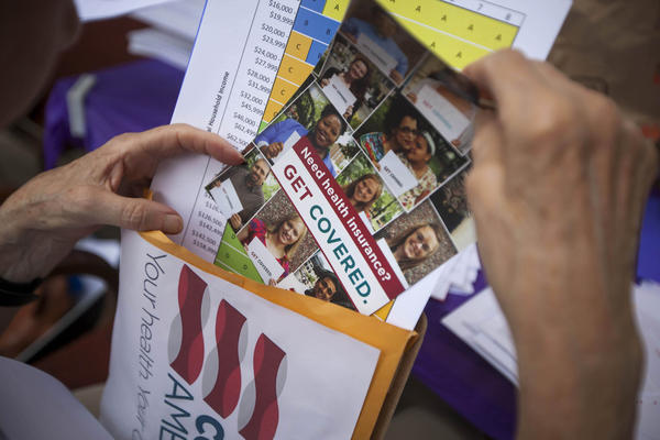 Margot Lee, a volunteer for Enroll America's Get Covered America campaign, organizes her materials before canvassing the neighborhood informing prospective health insurance consumers about new insurance possibilities available through the Affordable Care Act, in Englewood, New Jersey, U.S., on Saturday, July 27, 2013. The initiative aims to use tactics honed in U.S. President Barack Obama's presidential campaigns to ensure success for his signature health-care overhaul.