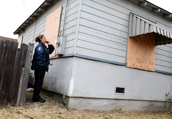 Code enforcement officer Lorena Burciaga calls in a utility meter number at a foreclosed home in Richmond, Calif.
