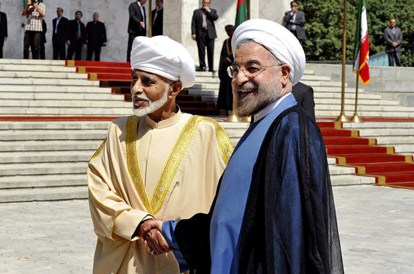 Iranian President Hassan Rouhani, right, shakes hands with Sultan Qaboos bin Said of Oman at an arrival ceremony in Tehran.