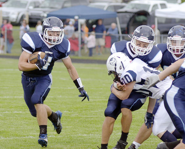 Petoskey senior running back Chase Ledingham (left) follows a pair of blockers during Friday's non-league contest against Sault Ste. Marie at Curtis Field. Ledingham scored three touchdowns as the Northmen defeated the Blue Devils, 23-7.