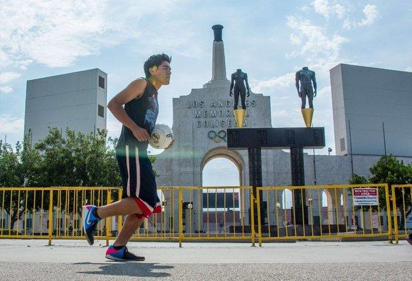 A runner jogs past the entrance to the L.A. Memorial Coliseum.