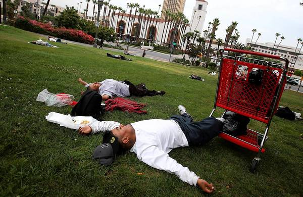 Homeless men get some sleep at Father Serra Park, across from Union Station.