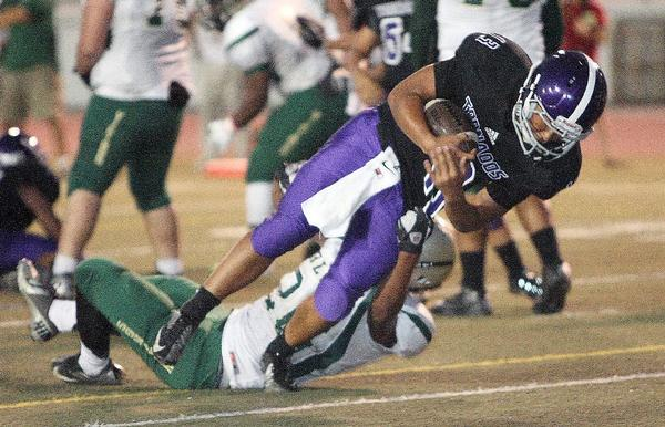 Hoover quarterback Se Jun Kim dives over a Blair defender for a one-yard touchdown plunge on Friday. Hoover romped over Blair, 65-0. (Roger Wilson/Staff Photographer)