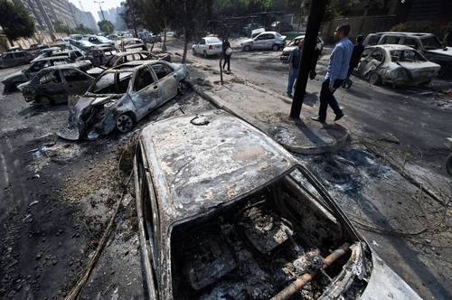 Egyptians pass by burnt vehicles outside the destroyed camp of ousted Mohammed Morsi supporters outside Rabaa al-Adawiya mosque in Cairo.