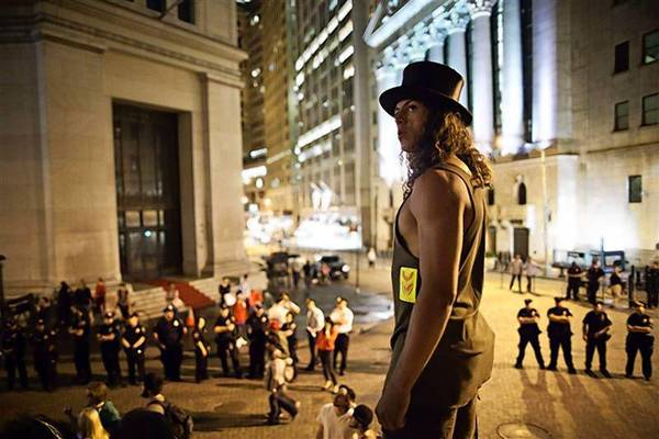 An Occupy Wall Street protester stands on the steps of Federal Hall, across the street from the New York Stock Exchange in April, 2012.
