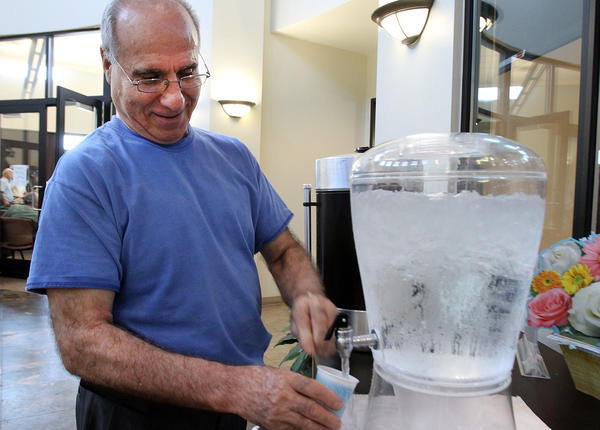 R. B. Bakahsi, of Glendale, fills a cup with ice water at the Adult Recreation Center in Glendale, a cooling station, on Friday, August 30, 2013.