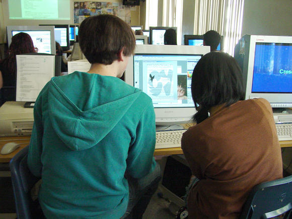 Two Crescenta Valley High School students add touch ups to the image projected on to their monitor. The Glendale Unified school board hired a company to monitor students' public posts on social networks, sparking mixed response from students. (File Photo)