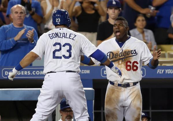 The Dodgers' Adrian Gonzalez, left, is congratulated by Yasiel Puig after hitting a two-run home run against the Padres in the seventh inning Friday. (Getty Photo)