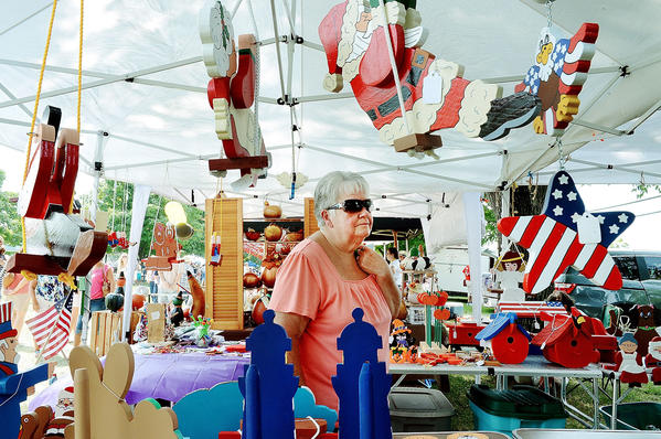 Jackie Dash of Williamsport looks over wood crafts by Bob Shank during Maugansville Pride Day on Saturday.