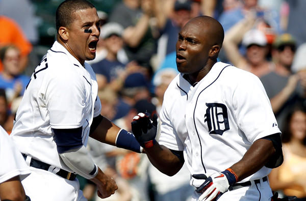 Tigers right fielder Torii Hunter is greeted at home plate by Victor Martinez and other teammates after hitting a three-run, walk-off home run against the A's on Thursday at Comerica Park in Detroit.