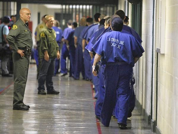 Inmates are watched by members of the Los Angeles County Sheriff's Department at the Men's Central Jail in Los Angeles. So far this year, the department has released more than 23,000 inmates before their jail terms were up.