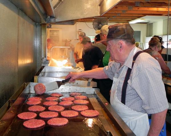 """Dave """"Sonny"""" Monn flips burgers at the Quincy Ox Roast on Saturday."""