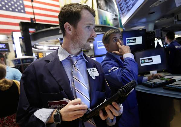 Trader Timothy Pastina, left, works on the floor of the New York Stock Exchange.