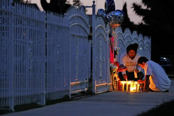 Benjy Ibarra, 15, and his friend Marlene Vazquez tend candles at a memorial for Benjy's brother Manny, 17, who was shot and killed as he rode his skateboard on the sidewalk along North Chester Street in Compton.