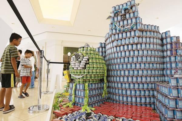 "Jeffrey Yang and his twin brother Jacob, 8, view a canned food structure called ""Scare Up Some Monstrous Eats"" at Canstruction Orange County at South Coast Plaza on Saturday."