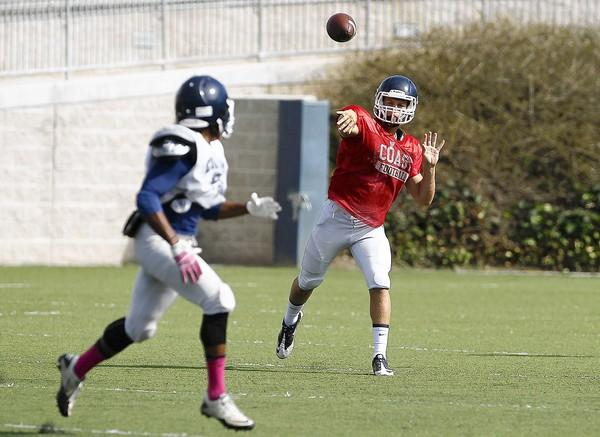 Orange Coast College's Jon Newsom throws to Treydonte Hill during an intrasquad scrimmage on Saturday.