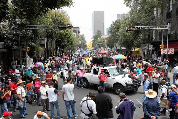 Members of a teachers union block a street Friday outside a government building in Mexico City. In another part of the city, thousands of the striking teachers have laid siege to the plaza surrounding the presidential National Palace.