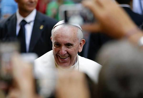 Pope Francis smiles as he arrives for a private visit at the Saint Agostino church in Rome.