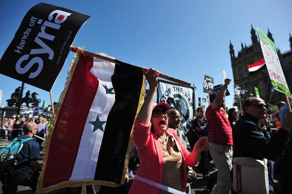 Protesters in London, some carrying the Syrian flag, demonstrate against military intervention in Syria.
