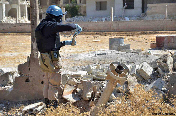 A member of U.N. investigation team takes samples of sands near a part of a missile outside Damascus.