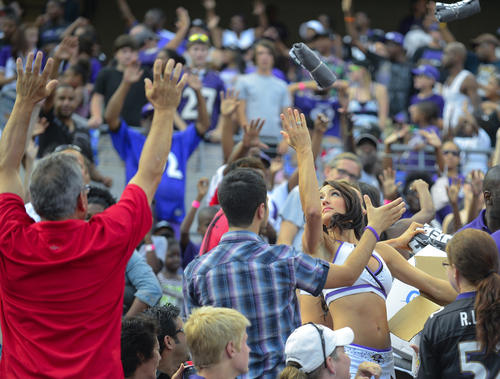 Ravens cheerleaders toss free gear to fans in the stands at M&T Bank Stadium.
