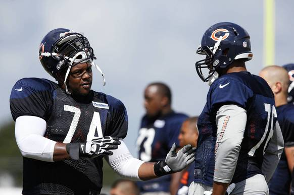 Bears tackle Jermon Bushrod (74) and Chicago Bears tackle Cory Brandon (76) talk technique.