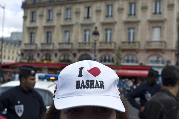 "A protester wears a cap declaring ""I [heart] Bashar"" during a demonstration in Paris on Saturday against French and foreign military involvement in Syria."