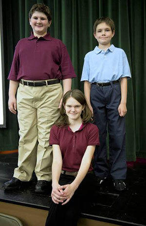 (Clockwise from left) Seventh-grader Ryan Wexler, fifth-grader Tyler Durgin and eighth-grader Victoria Durgin model new Allentown School District uniforms at an information session at South Mountain Middle School last week.