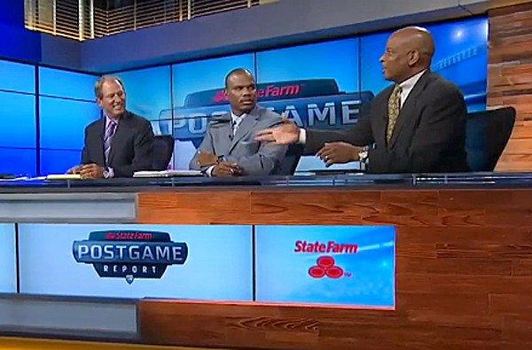 Former USC and NFL star Ronnie Lott, right, tosses his wallet toward former UCLA quarterback and coach Rick Neuheisel during the Pac-12 Network's postgame report Saturday night.