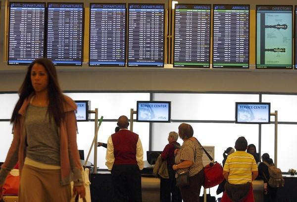 Customer service agents help passengers below a bank of screens showing departures and arrivals at Los Angeles International Airport.