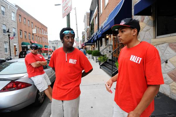Left to right, Jon Ritmiller, Reisterstown, Jereaux Embry, Towson, and Joshua Sewell, Baltimore, valets for restaurants in Little Italy, wait for customers. They say they are parking far fewer cars than is usual on a summer Saturday evening. Some speculate that the Grand Prix of Baltimore is affecting their business.