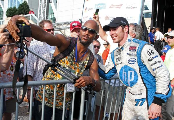 Simon Pagenaud, of France, driver of the #77 Schmidt Hamilton Motorsports Honda Dallara poses for a photo with a fan in victory lane after winning the Grand Prix of Baltimore on September 1, 2013 in Baltimore, Maryland.