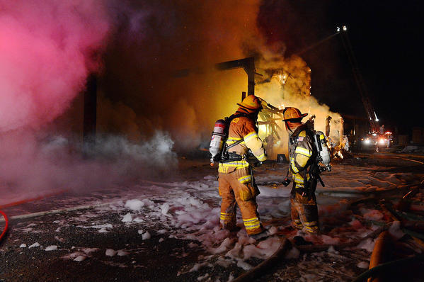 Firefighters work Sunday night at the scene of a fire in a lumber kiln building off Clear Spring Road (Md. 68) between Clear Spring and Williamsport.