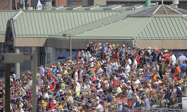 A crowd of people in the grandstands across from the Pratt Street Pavilion watch the IZOD IndyCar Series at the 2013 Grand Prix of Baltimore.