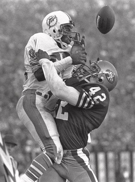 San Francisco 49ers safety Ronnie Lott, right, slams into Miami Dolphins receiver Mark Clayton during Super Bowl XIX in 1985. Lott is one of hundreds of former NFL defensive backs who have filed injury claims against their former teams.