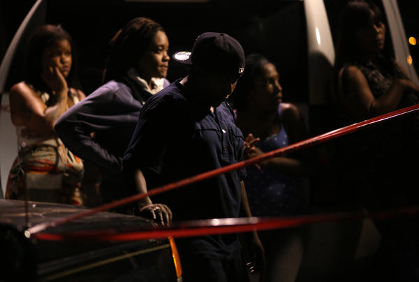 Family friends watch as police investigate the scene of the fatal shooting of a 25 year-old man on the 6400 block of South Morgan Street early Monday, Sep. 2, 2013. (E. Jason Wambsgans/Chicago Tribune)