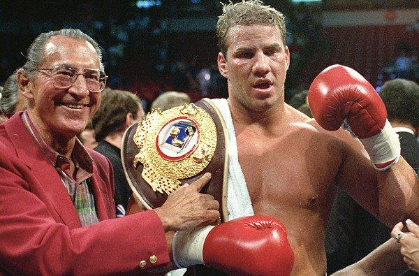 Tommy Morrison celebrates after defeating George Foreman for the WBO heavyweight title.