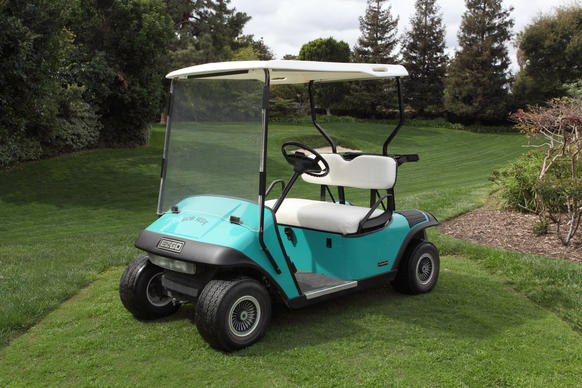 "A personalized turquoise E-Z-Go golf cart with removable hard-top roof, white upholstered bench seat and ""Bob Hope"" inscribed across the hood in black lettering.  <p><br>  