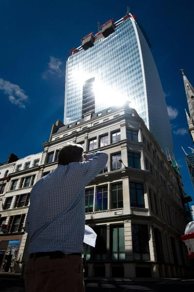 """A man reacts to a shaft of intense sunlight reflected from the glass windows of the new """"Walkie Talkie"""" tower in central London on August 30, 2013."""