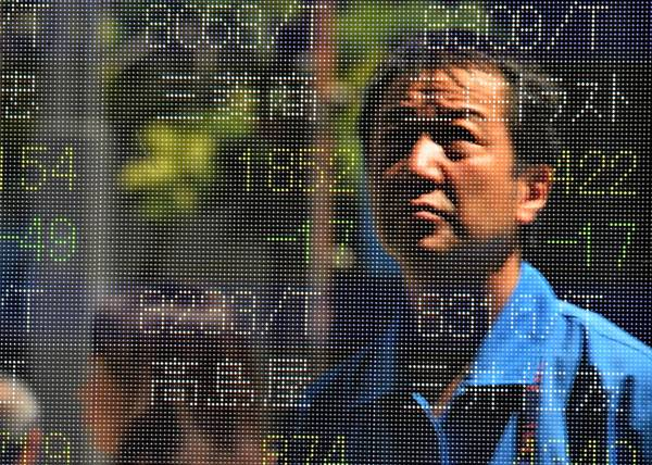 Japan's stock market has surged more than 50% in less than a year. Above, a man is reflected on a share prices board at the Tokyo Stock Exchange.