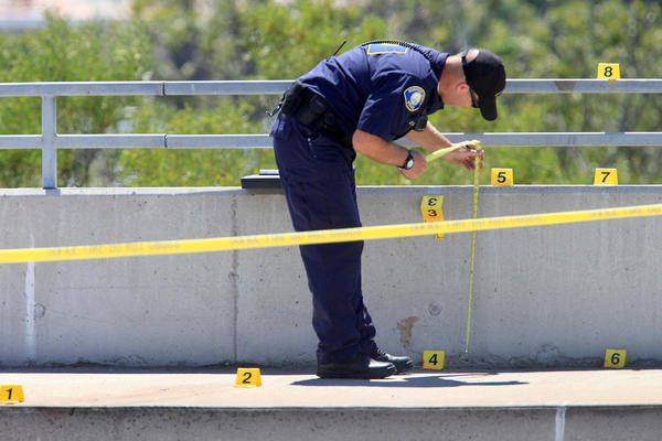 A Newport Beach Police Crime Scene Investigator takes notes along the eastbound side of Pacific Coast Highway, between Bayside Drive and Dover Drive, in Newport Beach on Labor Day. A female body was reported seen below Coast Highway.