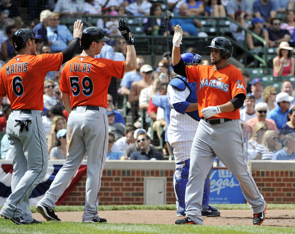 Sep 2, 2013; Chicago, IL, USA; Miami Marlins starting pitcher Henderson Alvarez (37) is greeted by third baseman Ed Lucas (59) and catcher Jeff Mathis (6) after hitting a three-run homer against the Chicago Cubs during the second inning at Wrigley Field. Mandatory Credit: David Banks-USA TODAY Sports ORG XMIT: USATSI-124418