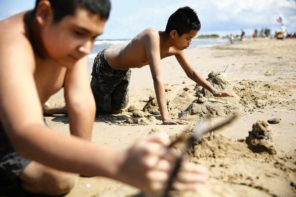 Moises Ponce, 11, center, and his cousin Jessie Jimenez, 13, left, play in the sand Monday at Montrose Beach in Chicago. High winds prompted a swim advisory on many of the city's beaches.