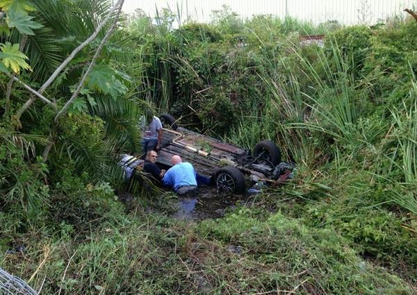 Michael Clancy looks back at I-95 to see if more help is coming to free Phenise Louis who was trapped in an overturned car in a water-filled drainage ditch in Fort Lauderdale